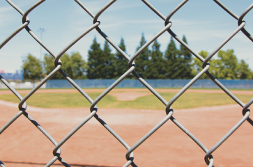 chain-link-fence-in-the-back-of-a-baseball-field-used-to-protect-fans-from-foul-bouls-and-create-a-perimeter